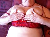 Granny in red bra and thong caressing her big tities