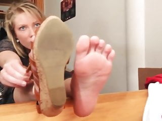 Pretty blonde removes wedge sandals and shows sweet soles.