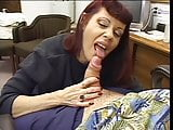 Redhead gives blowjob and boob job to old guy in office